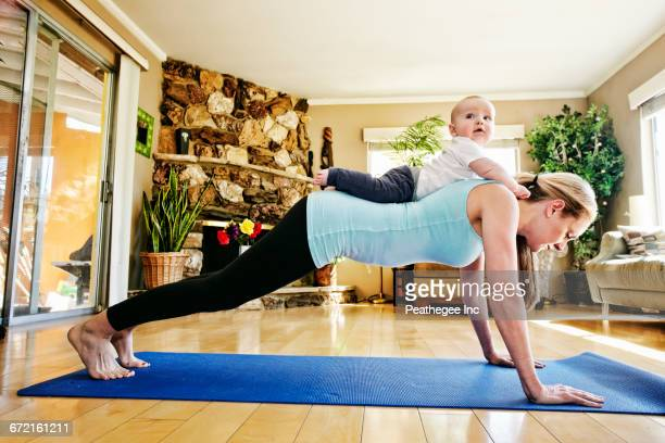 Mother working out on exercise mat with baby on back