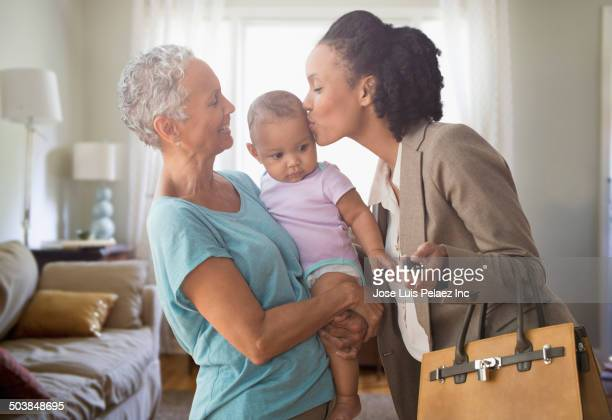 Mother working while grandmother plays with baby
