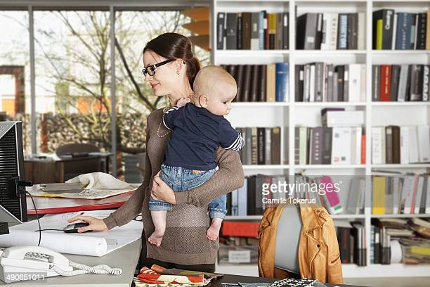 Mother working while holding baby
