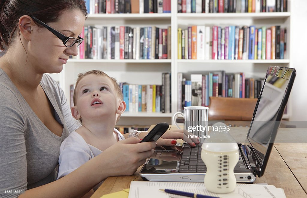 mother working/studying with baby : Stock Photo
