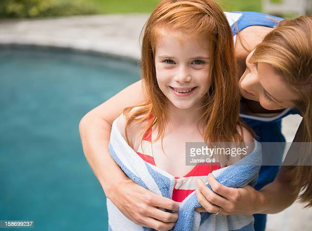 Mother wrapping daughter in towel