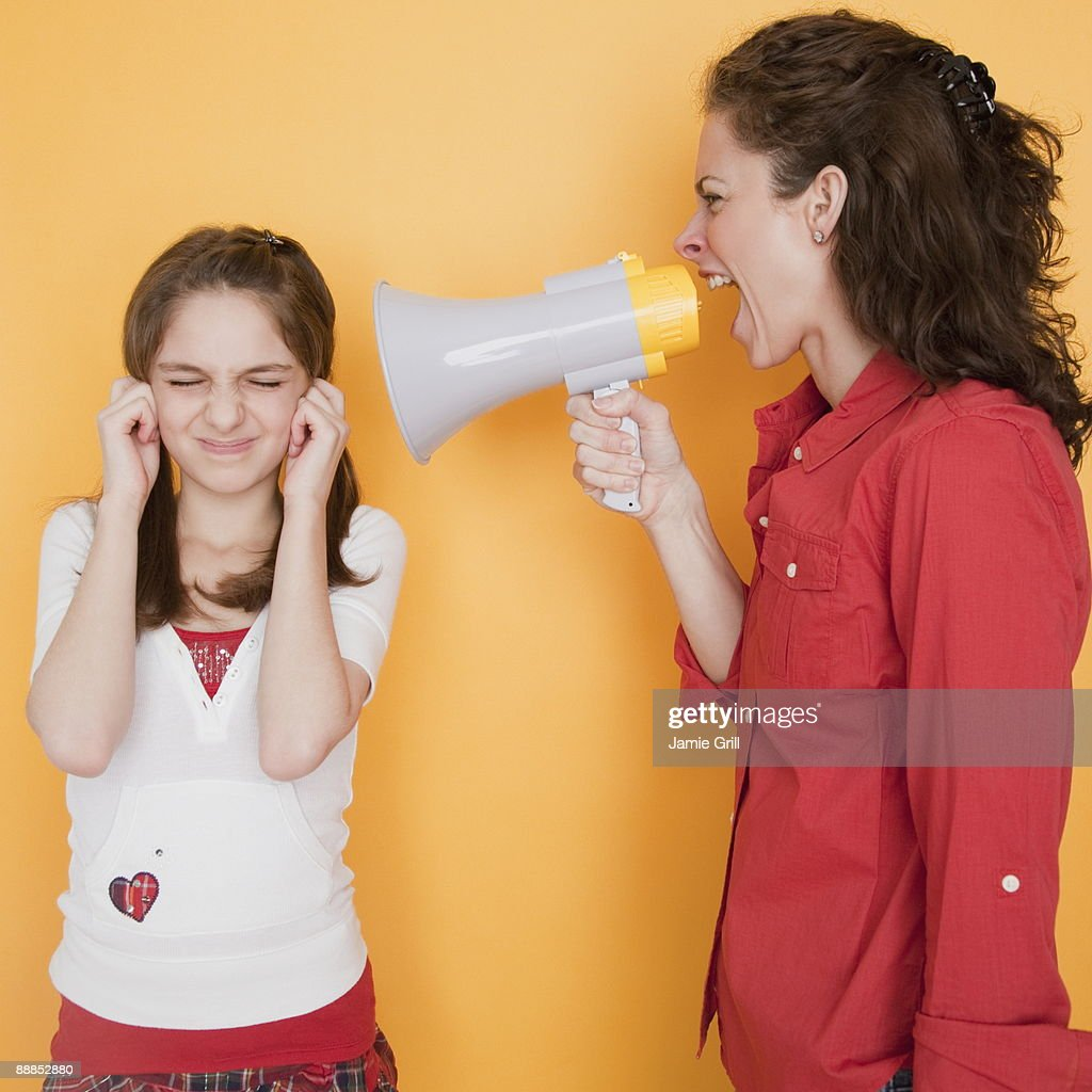 Mother yelling at daughter (10-11 years) through megaphone : Stock Photo