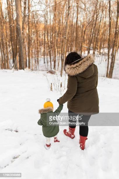 オハイオ州で2020年のクリスマスの日にふわふわした白い雪の中を歩く赤いブーツ&グリーンジャケットを着た母親と若い幼児の娘 - ブーツイン ストックフォトと画像