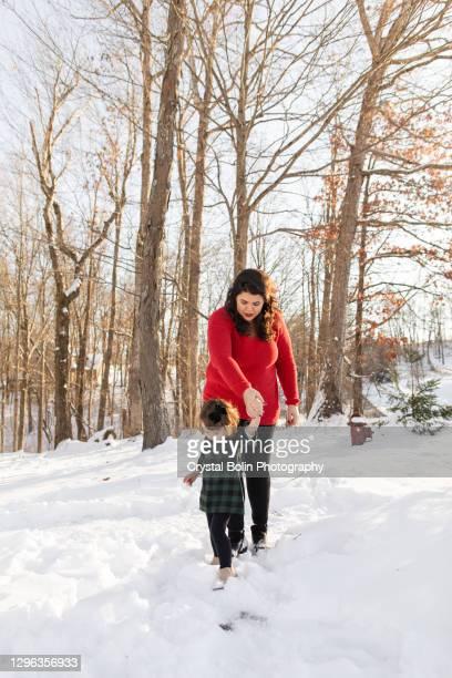 オハイオ州のクリスマスの日にふわふわした白い雪の中を歩く母と若い幼児の娘 - ブーツイン ストックフォトと画像