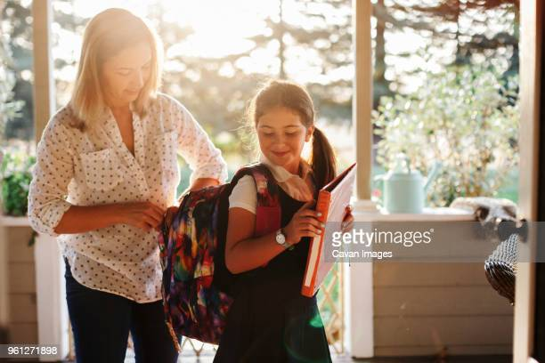 mother zipping daughters backpack while standing in porch - preparation stock pictures, royalty-free photos & images