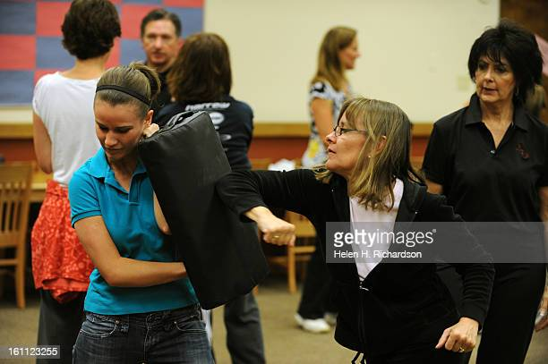 Motherdaughter team Lindsey Bell left uses a pad while her mother Edie Bell practices using her elbow and forearm as defense while instructor...