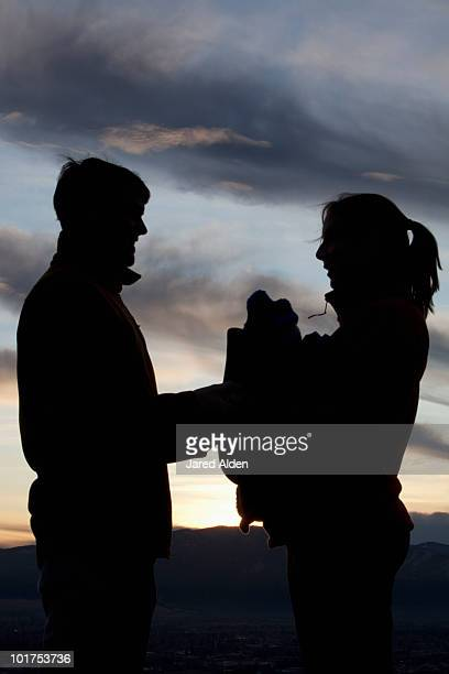 Mother,father and baby in front carrier silhouetted against beautiful sunset.