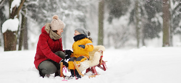 Mother/nanny talk with small child during sledding in winter park 1060437696
