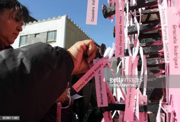 Mothers and activists place the names of women murdered in Ciudad Juarez around a black cross on the Paso del Norte International Bridge during a...