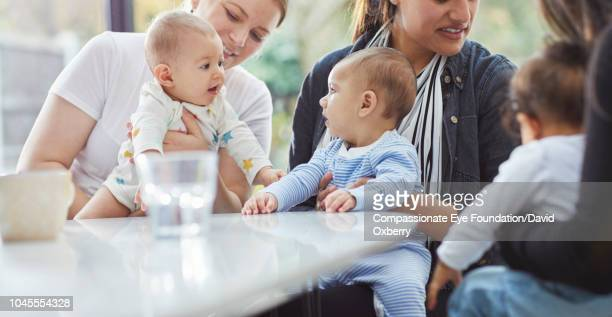 Mothers and babies in kitchen