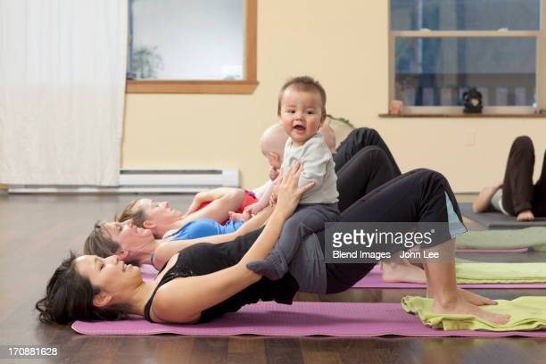 Mothers and babies taking yoga class