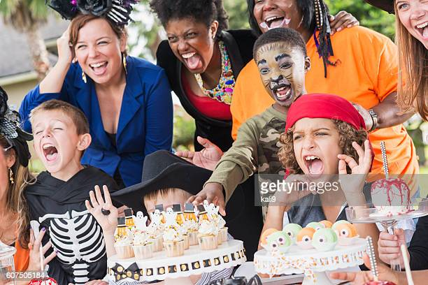 mothers and children at a halloween party - halloween party stock photos and pictures