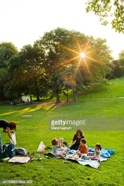 Mothers and children (4-9) having picnic in park