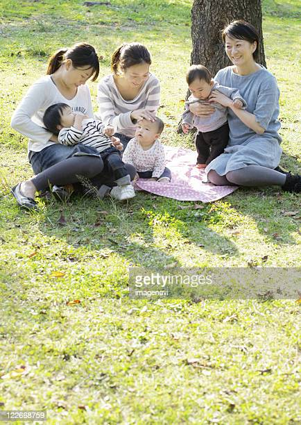 Mothers and children playing on grass