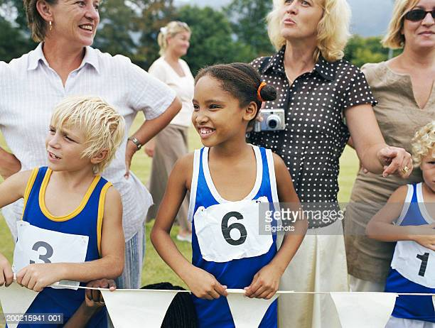 Mothers and children (5-9) watching school sports day event