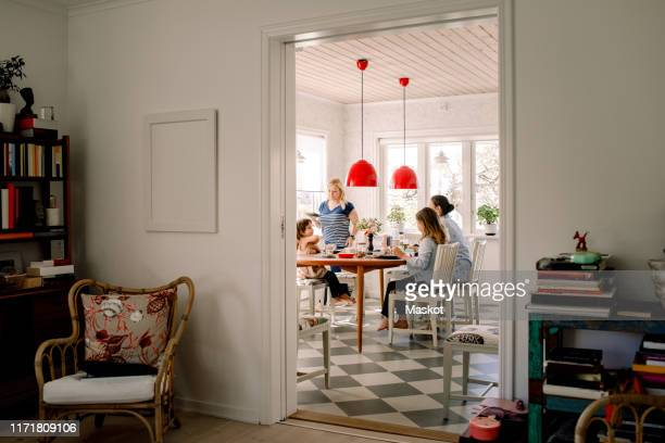 mothers and daughters having breakfast at dining table seen through doorway - lgbtq  and female domestic life fotografías e imágenes de stock
