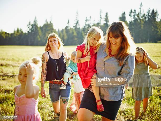 Mothers and daughters walking through field