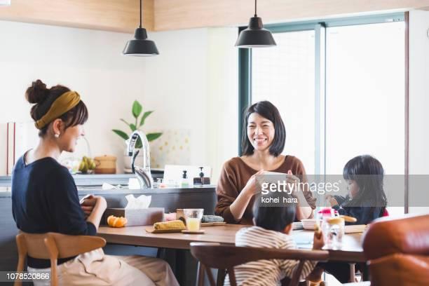 母親と子供がダイニング テーブルで食事 - 親睦会 ストックフォトと画像