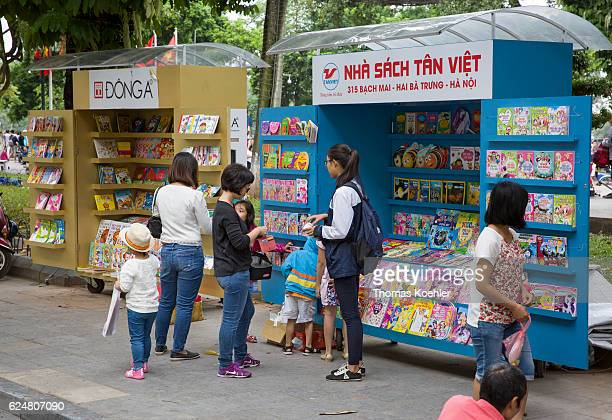 Mothers and their children are standing in front of mobile sales stands for books on a street in Hanoi on October 30, 2016 in Hanoi, Vietnam.