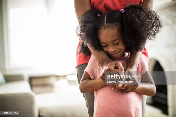 mother's arms embracing daughter - afro amerikaanse etniciteit stockfoto's en -beelden