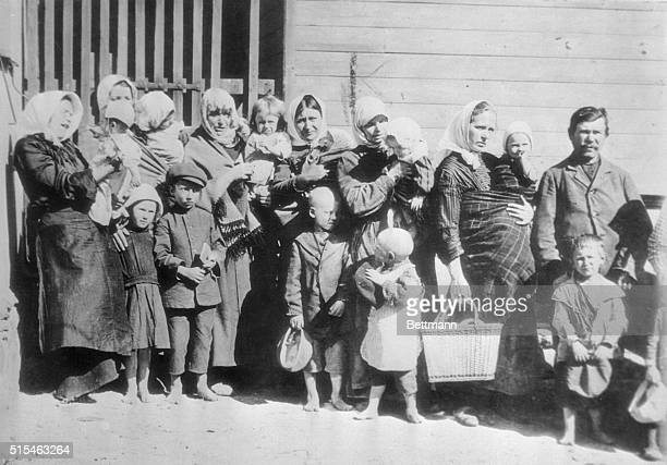 Mothers, babes in arms, other children shoeless, standing in breadline in Latvia, then a part of Russia. It was a tedious wait, but the impoverished...