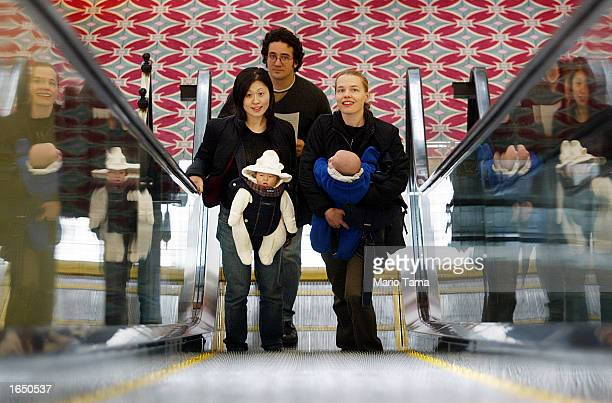 Mothers carry their babies up an escalator on their way to watch the movie 'Comedian' with other moms and babies during the Reel Moms event November...