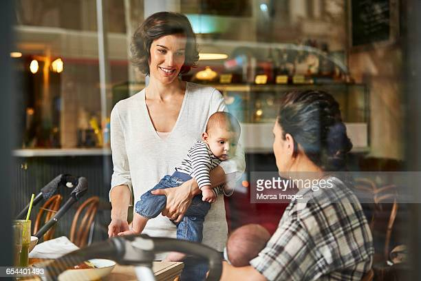 Mothers carrying babies in restaurant