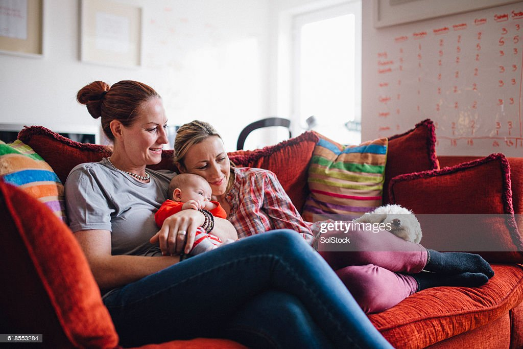 Same sex couple enjoying a cuddle together at home, with their baby daughter and their pet dog.
