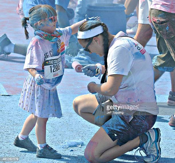 A mother's daughter rubs blue chalk into her hair at one of the chalk stations along the five kilometer course during The Color Run presented by...