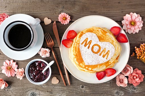 Mothers Day breakfast pancakes with heart shape and MOM letters, overhead view table scene on rustic wood 1214317025