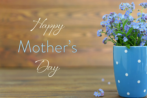 Mothers Day card with flowers in the cup on wooden background 1145527307