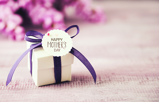 Mother's Day gift box with purple ribbon and wisteria bouquet 1148437898