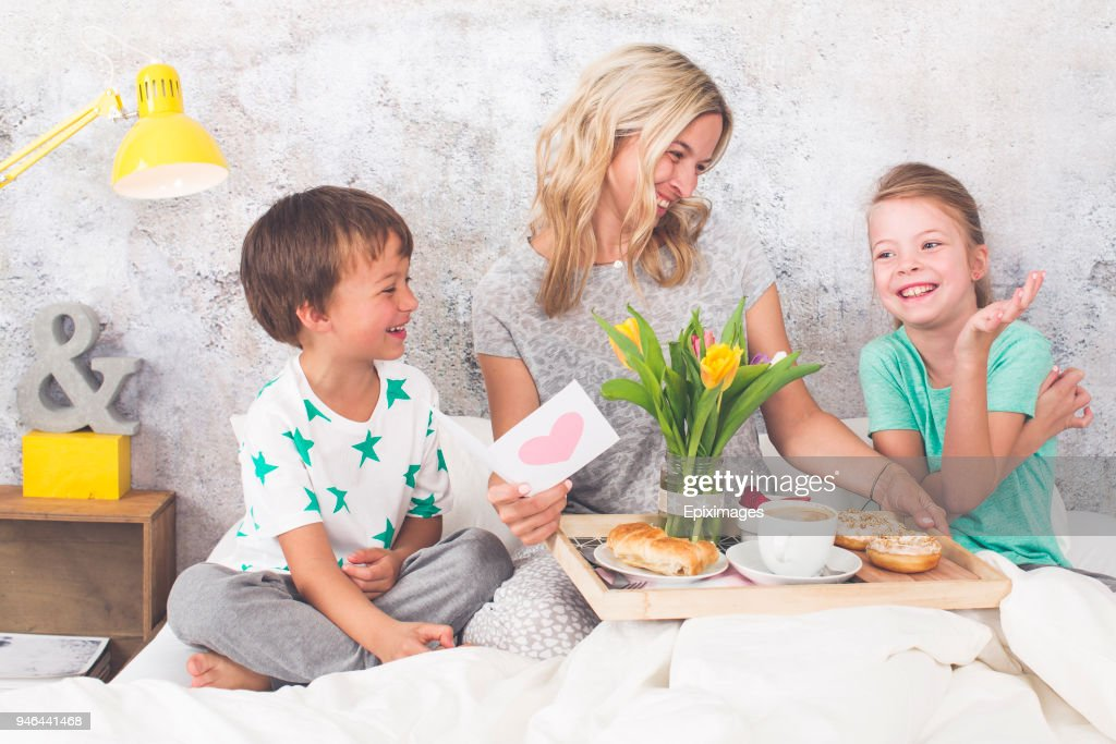 Mother´s Day - two children surprise their mother with breakfast in modern bed : Stock Photo