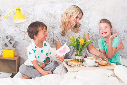 Mother´s Day - two children surprise their mother with breakfast in modern bed 946441468