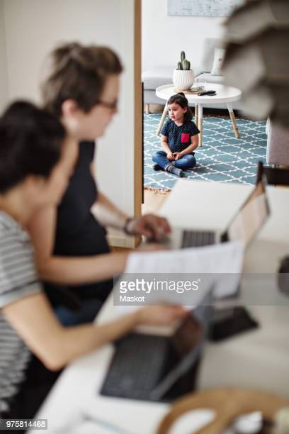 Mothers discussing over financial bills while daughter sitting in living room at home