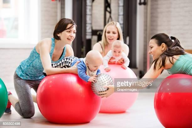 Mütter mit Babys im Fitnessstudio auf Gymnastikbällen Ausübung.