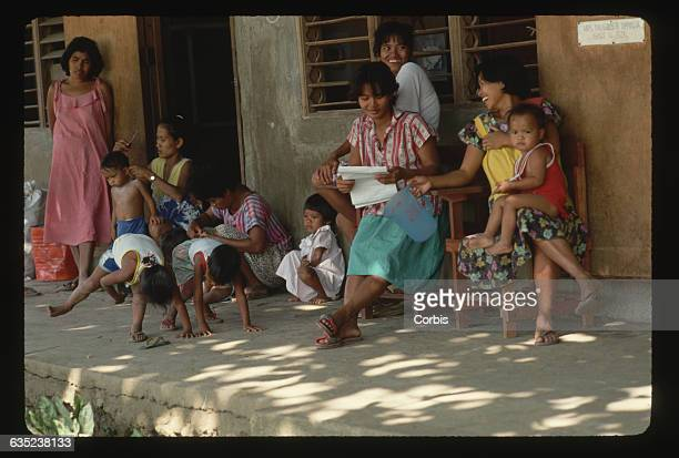 Mothers give their boys haircuts at an evacuation camp The had to leave Volcano Island before the Taal Volcano erupted | Location Venancio Trinidad...