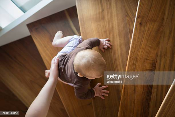 Mothers hand helping baby girl climbing up a stair