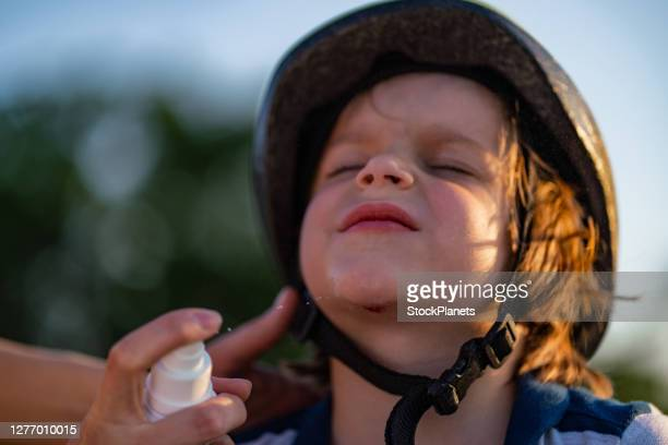 mother's hand puts disinfectant on the wound on son's chin - chin stock pictures, royalty-free photos & images