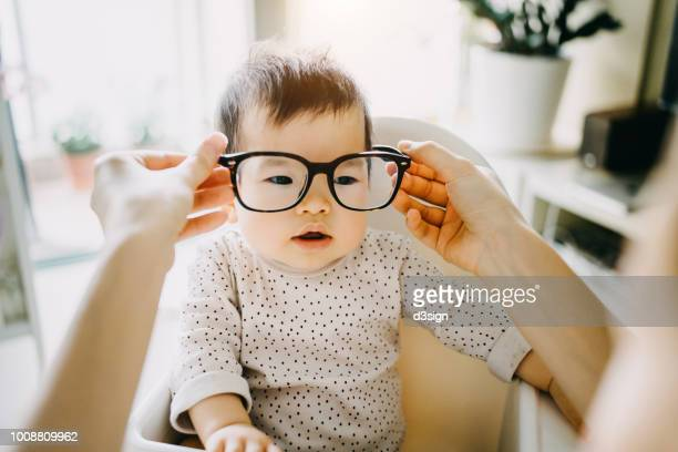Mother's hand putting on oversized glasses onto baby girl