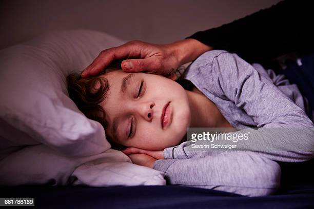 Mothers hand stroking sleeping boy