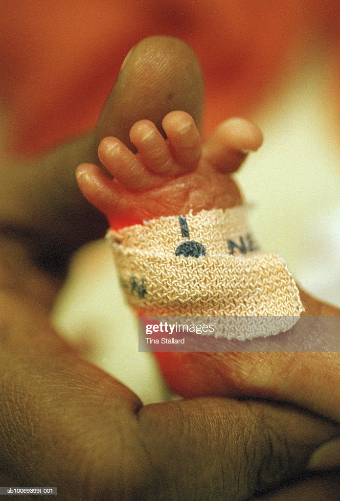 DECEMBER 2004, LONDON, ENGLAND, A mother's hand stroking the foot of her premature baby daughter in the intensive care baby unit at St Mary's Hospital, Paddington. An oxygen probe is taped to her tiny foot, giving it a red glow.