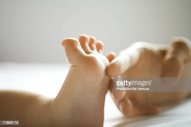 Mother's hand tickling baby's foot, close-up