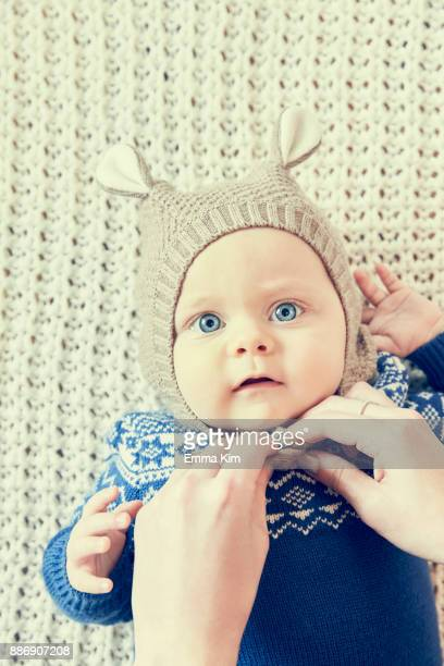Mothers hands fastening baby sons knitted hat with ears