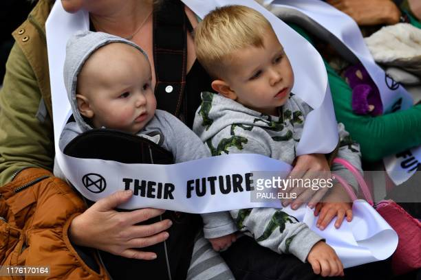 Mothers hold their babies as they protest about the climate crisis outside Google offices during the tenth day of demonstrations by the climate...