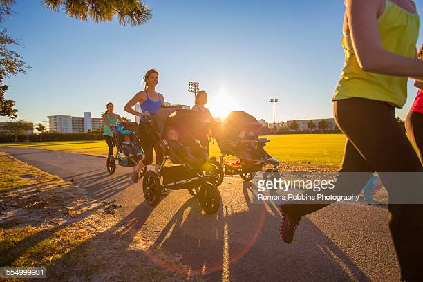 Mothers jogging in park with pushchairs