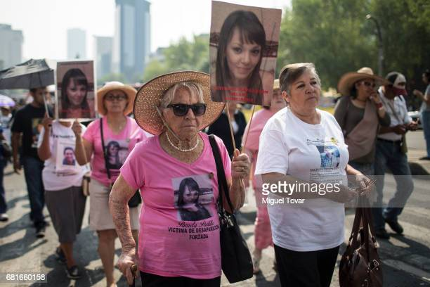 Mothers of a disappeared holds up signs with images of their missing relatives during a march on Mother's Day on May 10 2017 in Mexico City Mexico...