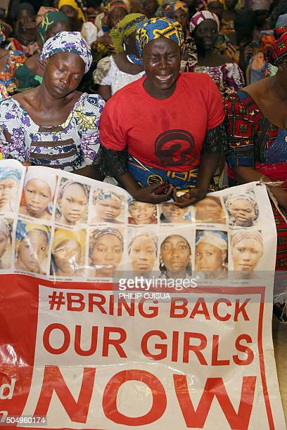 Mothers of missing girls kidnapped in 2014 from their school in Chibok by Islamist group Boko Haram holding a banner showing photographs of the girls...
