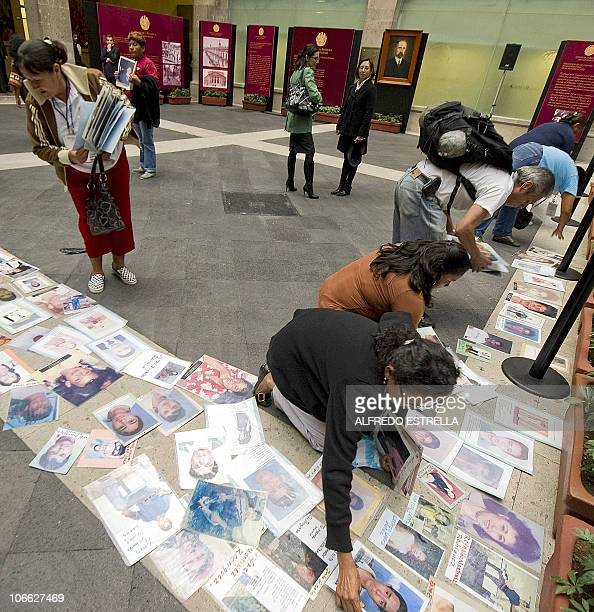 Mothers of missing immigrants from Honduras place pictures of their children on the floor during a demonstration outside of the Mexican Senate in...