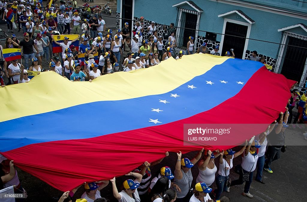 Mothers of Venezuelan anti-government students hold a Venezuelan national flag during a protest against the government of Venezuelan President Nicolas Maduro in San Cristobal, capital of the western border state of Tachira, Venezuela, on February 21, 2014. At least eight people have been killed, 137 wounded and more than 100 detained in the protests shaking Venezuela, officials said Friday, confirming a jump in the death toll. AFP PHOTO/Luis ROBAYO